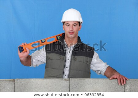 Man stood by wall with spirit-level Stock photo © photography33