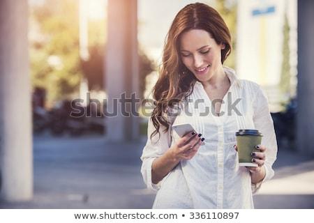 Młoda kobieta sms komórkowych ekran dotykowy telefonu Zdjęcia stock © stokkete