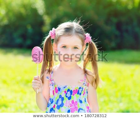 Kislány tart nyalóka citromsárga édes cukorka Stock fotó © lovleah