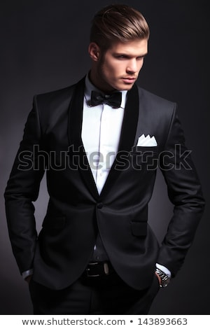 man wearing tuxedo standing with hands in pockets looks up stock photo © feedough