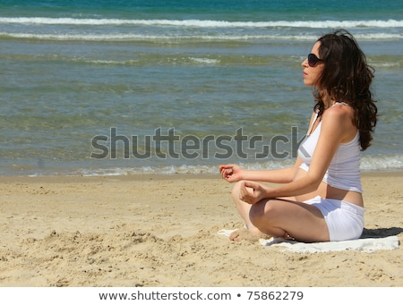a pregnant woman doing yoga on the beach stock photo © adrenalina