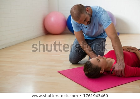 Yoga instructor guiding student in exercising at club Stock photo © wavebreak_media