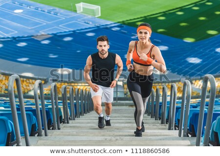 sportswoman and sportsman jogging on stairs stock photo © LightFieldStudios