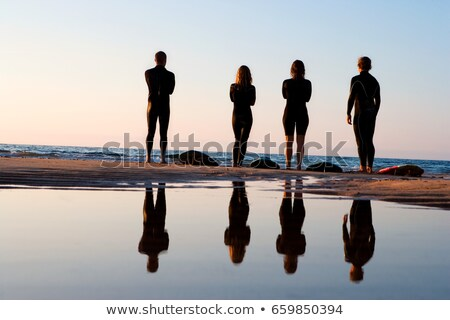 Quattro persone piedi spiaggia cielo acqua sabbia Foto d'archivio © IS2