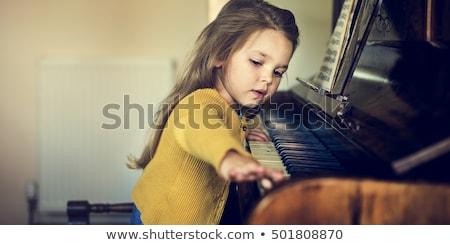 Schoolgirl playing piano in music class Stock photo © monkey_business