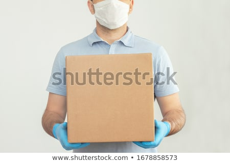 delivery man carrying cardboard boxes on hand truck stock photo © andreypopov