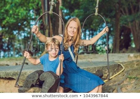 Mom and son swinging on an old swing against the background of the roots of the tree Stock photo © galitskaya