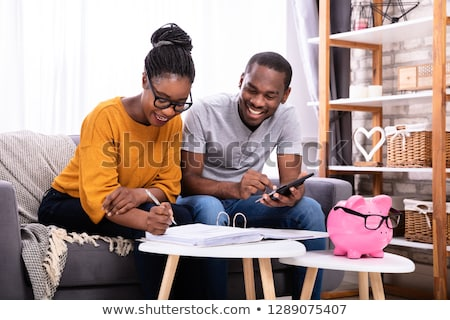 African Couple Calculating Invoice With Calculator Stock photo © AndreyPopov