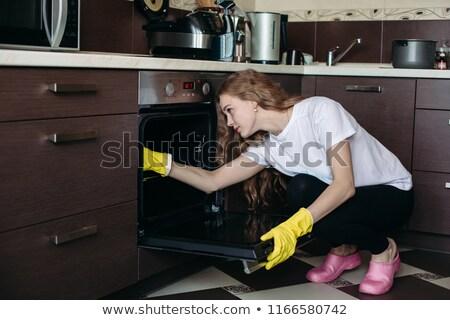 Dziewczyna kręcone włosy mycia piekarnik kuchnia Zdjęcia stock © studiolucky