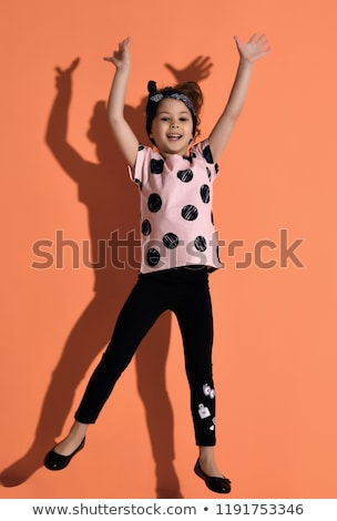 A Cute girl 5 year old posing in studio pointing Stock photo © Lopolo