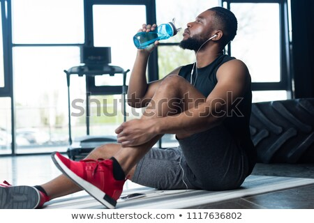 Handsome young sportsman in earphones holding fitness mat Stock photo © deandrobot
