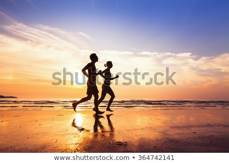 Silhouette Of A Couple Running On The Beach At Sunset Stock photo © AndreyPopov