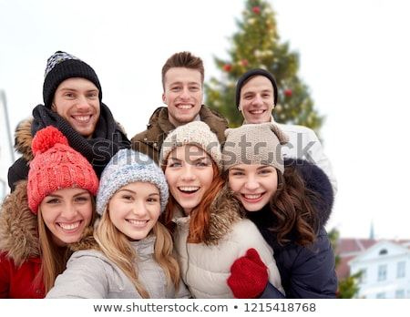 happy friends over christmas tree in old tallinn stock photo © dolgachov