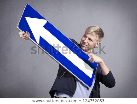 Friendly man holding upward pointing direction arrow sign. Stock photo © lichtmeister
