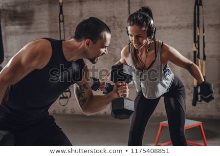 couple with dumbbells exercising in gym stock photo © dolgachov