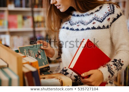 Young Woman Choosing A Book In Bookstore Stock photo © HighwayStarz