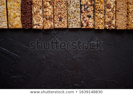 Various healthy granola bars placed in a row on black stone table Stock photo © dash