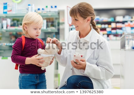 Pharmacist woman with child customer and her plush toy Stock photo © Kzenon