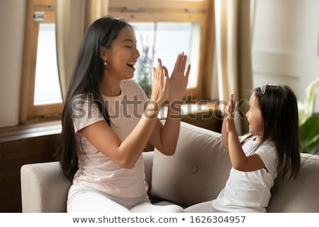happy little sisters playing clapping game at home Stock photo © dolgachov