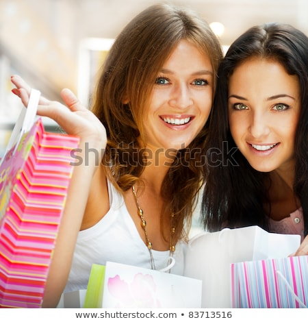 Two excited shopping woman resting on bench at shopping mall loo stock photo © HASLOO