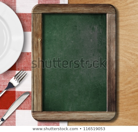 Menu blackboard lying on old  wooden table with knife and fork Stock photo © inxti
