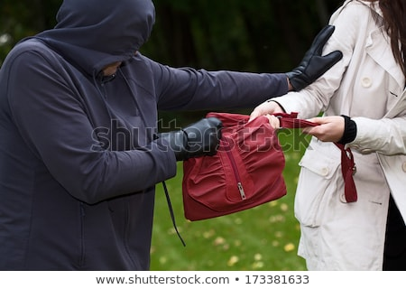 man pickpocketing a purse from woman's bag  Stock photo © dacasdo