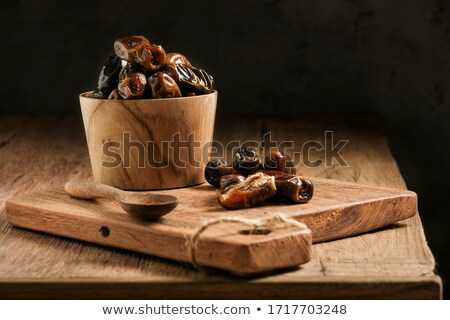 Dried dates in a rustic bowl. Typical arabian sweet fruit. Stock photo © Photooiasson