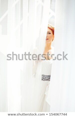 Lovely woman hiding behind white curtains Stock photo © deandrobot
