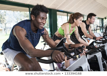 African woman in gym spinning on fitness bike Stock photo © Kzenon