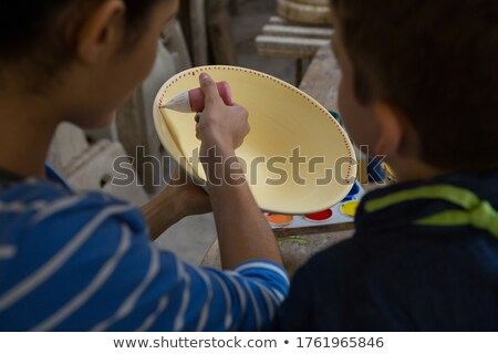 Female potter assisting her son in painting a bowl Stock photo © wavebreak_media