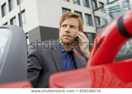 Man on phone in his electric sports car Stock photo © IS2
