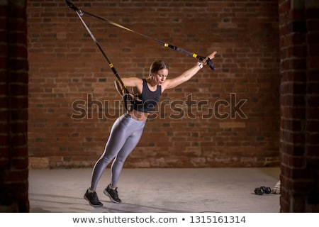 Attractive young woman working out on weight lifting training ma Stock photo © boggy