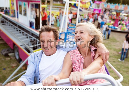 Happy couple riding a rollercoaster Stock photo © Minervastock