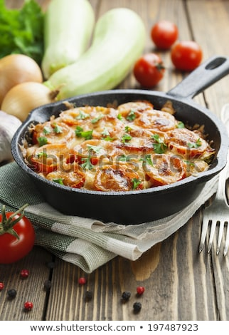Frying pan with fried tomatoes, zucchini, cheese and herbs on wooden cutting board stock photo © Virgin