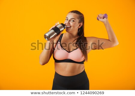 Portrait of young chubby woman in sportive bra drinking water fr Stock photo © deandrobot