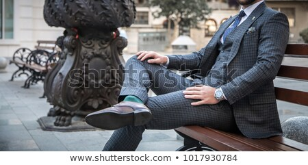 elegant man sitting, holding a hand on his leg Stock photo © feedough