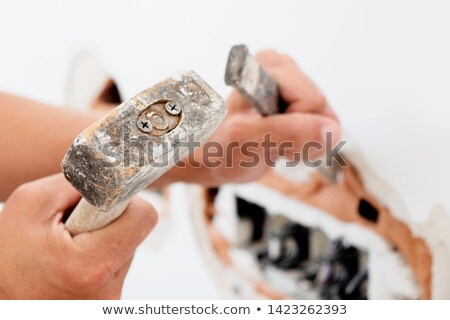 man using making a hole in a wall with a chisel Stock photo © nito