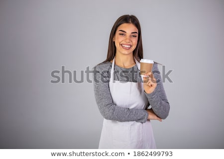 Happy brunette waitress in apron offering you glass of coffee or milk cocktail Stock photo © pressmaster