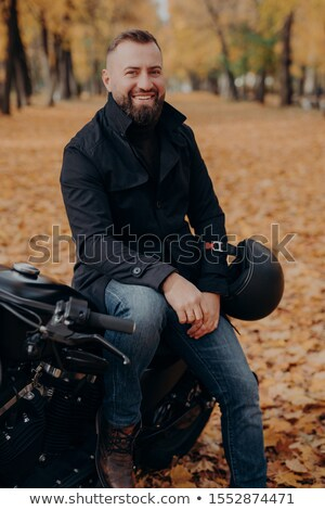 Vertical image of smiling motorcyclist smiles happily, holds helmet, poses on motorbike, wears black Stock photo © vkstudio