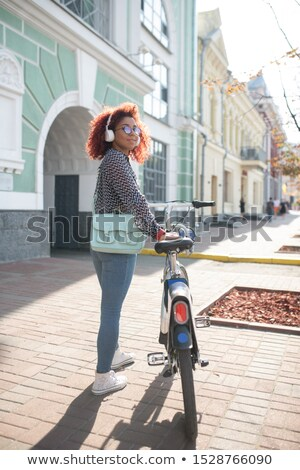 A student girl with a good mood goes near the building with stone steps Stock photo © ElenaBatkova