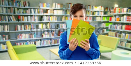 shy student boy hiding behind books at library Stock photo © dolgachov