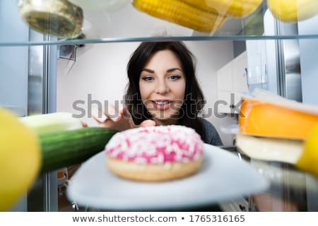 Happy Young Woman Taking Donut From Refrigerator Stock photo © AndreyPopov