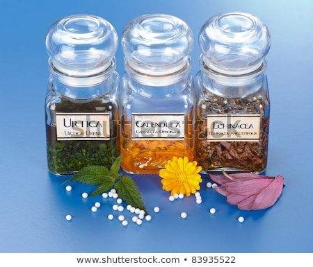 Homeopathic pills in front of Calendula plant extract Stock photo © erierika