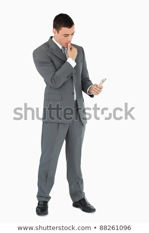 Businessman taking a close look at banknotes against a white background stock photo © wavebreak_media