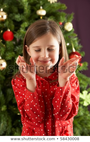 Young Girl Crossing Fingers In Front Of Christmas Tree Stock photo © monkey_business