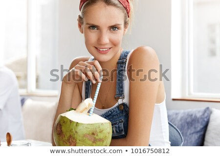 Beautiful woman sipping a coconut cocktail Stock photo © dash