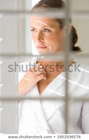 Vertical image of woman in bathrobe standing sideways Stock photo © deandrobot