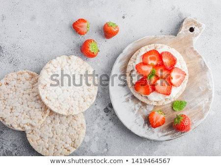 healthy organic rice cakes with ricotta and fresh strawberries and glass of milk on light stone kitc stock photo © denismart