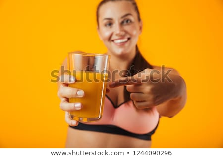 Image of joyful chubby woman in tracksuit smiling and holding gl Stock photo © deandrobot
