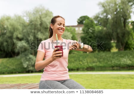 woman with shake looking at smart watch in park Stock photo © dolgachov